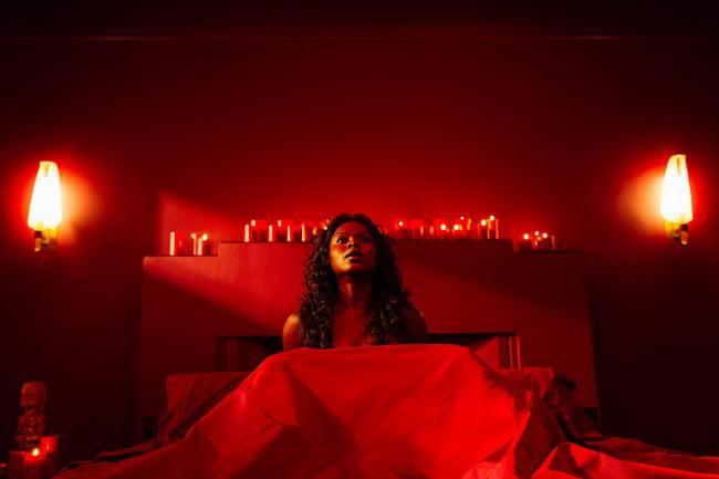 Bilquis im Bett in einem Zimmer mit roter Beleuchtung