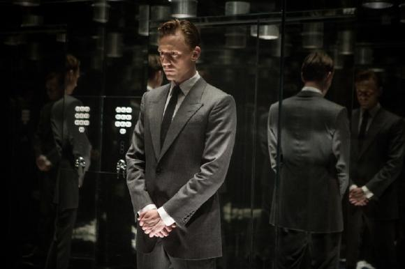Tom Hiddleston in Anzug und zurückgekämmten Haaren in einem verspiegelten Aufzug