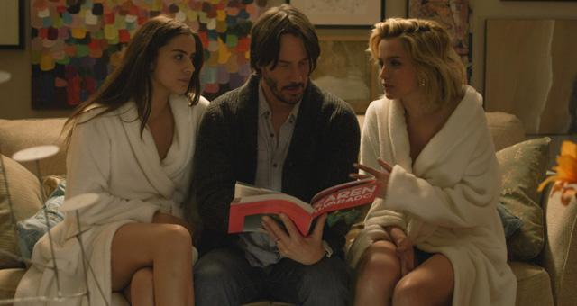 Keanu Reeves mit zwei Frauen auf dem Sofa