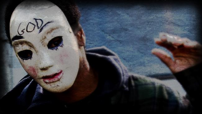 Typ mit weißer Maske, auf der GOD steht