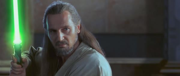 Liam Neeson als Qui-Gon Jinn mit erhobenem Lichtschwert