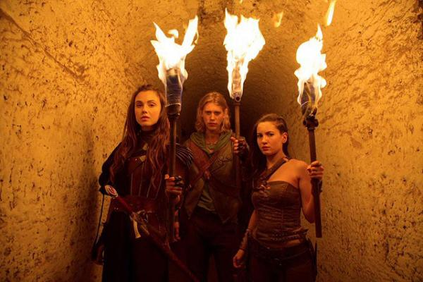 Shannara-Hauptcharaktere mit Fackeln in Katakomben