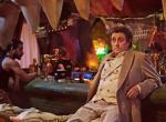 Ian McShane als Mr. Wednesday sitzt an einer Krokodilkopf-Bar